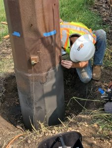 Contractor fixing corrosion on steel pole
